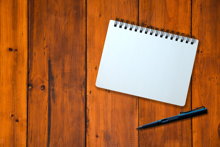 White page of notebook and black pen on wood pattern photo