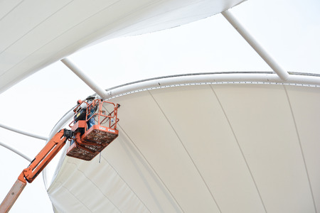 Technician install tensile fabric structure