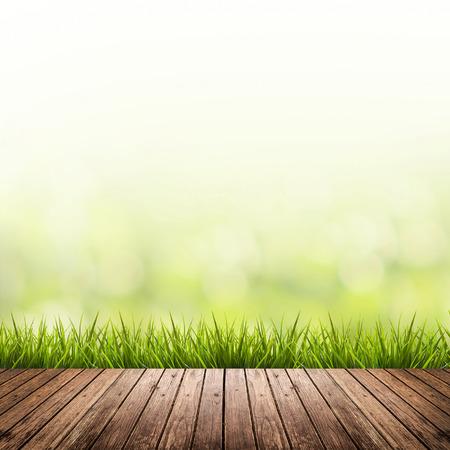 ぼやけている緑の自然背景と木製の床で新鮮な春の草 写真素材