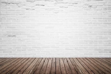 Antiguo espacio interior con pared de ladrillo blanco roto y el grunge piso de madera de la textura