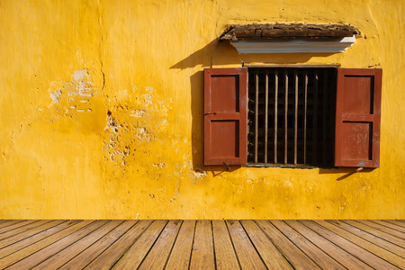 yellow house: opened antique window on the old grunge yellow wall and wood floor pattern for background
