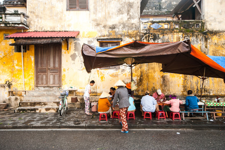 street vendor: HOI AN VIETNAM  OCTOBER 242012 : Vietnamese people in street food cafe on sidewalk at Hoi An ancient town of Vietnam
