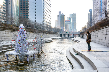 south space: SEOUL, SOUTH KOREA - OCTOBER 3, 2014 : People at Cheonggyecheon stream in winter. The stream is a modern public recreation space in downtown Seoul, South Korea. Editorial