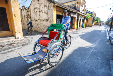 unidentified: HOI AN, VIETNAM - OCTOBER 24, 2012 : Unidentified man riding a traditional cyclo in Hoi An, Vietnam