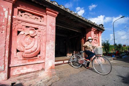 ponte giapponese: Hoi An, Vietnam - 24 ottobre 2012: la donna non identificata cavalcare la bicicletta a Ponte giapponese di Hoi An, Veitnam. Editoriali