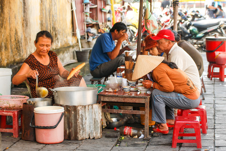 HOI AN, VIETNAM - OCTOBER 24,2012 : Vietnamese people in street food cafe on sidewalk at Hoi An ancient town of Vietnam