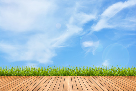 Wood texture terrace with fresh green grass under the blue sky and clouds of summer, use for background
