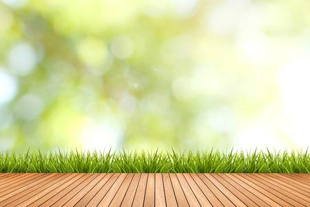 新鮮な春草緑の自然がぼやけて背景と茶色の木の床