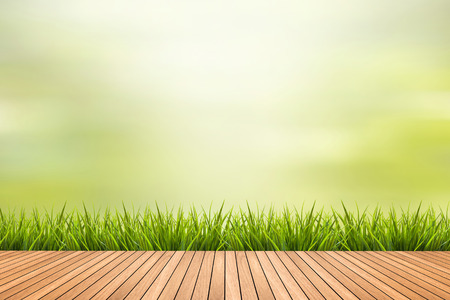 Fresh spring grass with green nature blurred background and brown wood floor Zdjęcie Seryjne