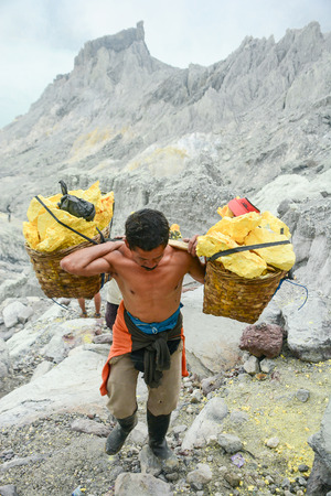 KAWAH IJEN, INDONESIA - JANUARY 22, 2013 : Miner carry baskets with sulfur sulphur from the sulfur mines in the crater of the active volcano of Kawah Ijen, East Java, Indonesia.