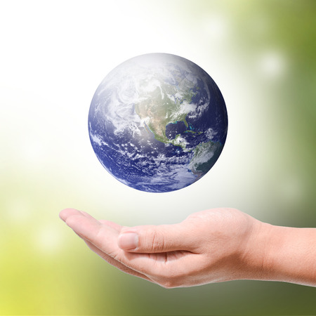green tone: Male hands holding the Earth on light green tone background.