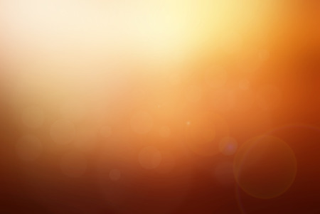 Abstract sunset tone blurred background. brown, red, orange and yellow with bright sunlight, flare and bokeh effect. use for backdrop or web design in summer sunset concept. 免版税图像