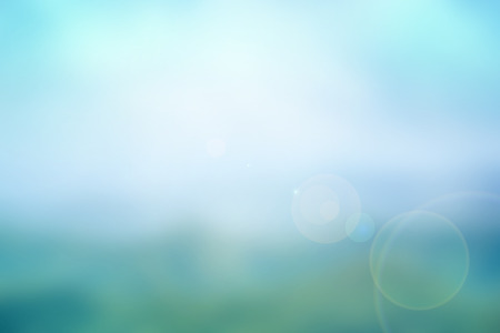 Abstract nature blurred background in blue-turquiose tone with bright sunlight, flare and bokeh effect Stock Photo
