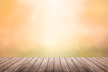Brown wooden floor with abstract orange blurred background in sunset tone color and sunlight on top