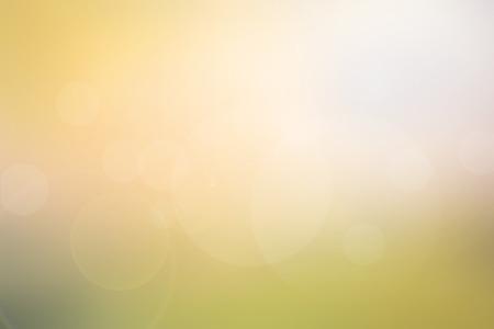 明るい日光、フレア、ボケ味の効果で暖かいトーンの抽象的な光の黄緑の被写体の背景