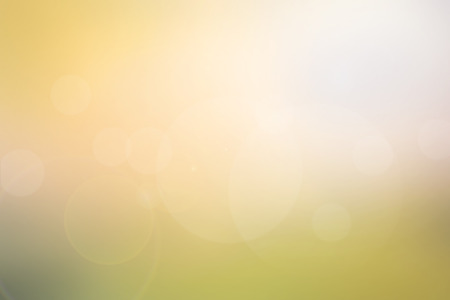 Abstract light yellow-green blurred background in warm tone with bright sunlight, flare and bokeh effect