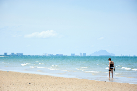 huahin: woman in swimsuit walk on the beach, beautiful tropical sea in summer of Huahin, Thailand Stock Photo