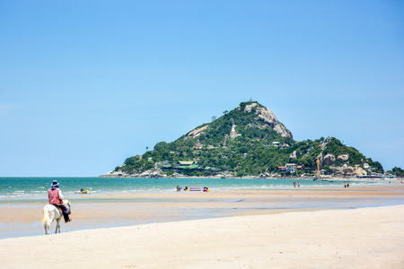 hua hin: man ride the white horse on the beach of Khao Takiab, tropical sea of Hua Hin District,Thailand