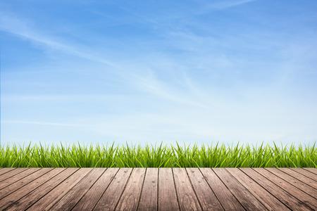cielo con nubes: Textura del suelo de madera de la terraza con la hierba verde fresca bajo el cielo azul, las nubes y la luz del sol del verano Foto de archivo