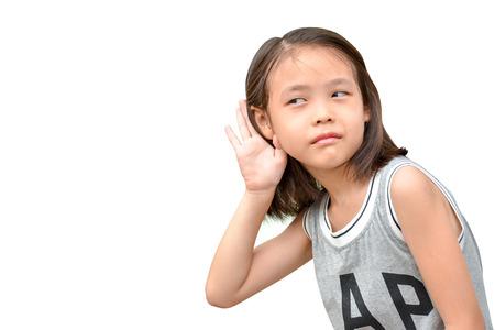 liitle かわいい女の子聞いて聞いたり何か、白い背景で隔離のアジア子供の肖像画 写真素材
