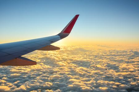 翼飛行機の窓から見る美しい夕焼け空と雲に飛行機の 写真素材