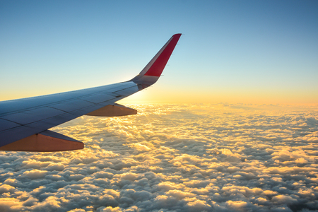 Wing of plane on beautiful sunset sky and clouds, view from window of the airplane Stockfoto
