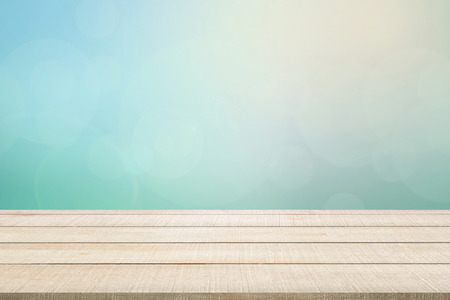Beige wood table top panel on pastel blurred background in blue-turquoise tone with bright sunlight and flare, use for display or montage products for advertisement in natural summer concept Stock Photo