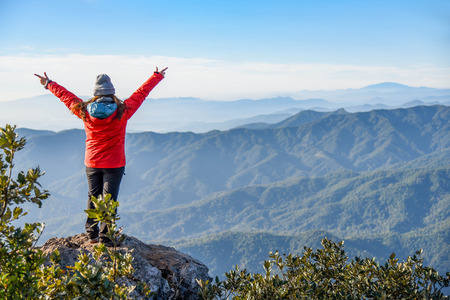 upraised: Woman traveler in red coat upraised arms on top of mountain among beautiful spring landscape