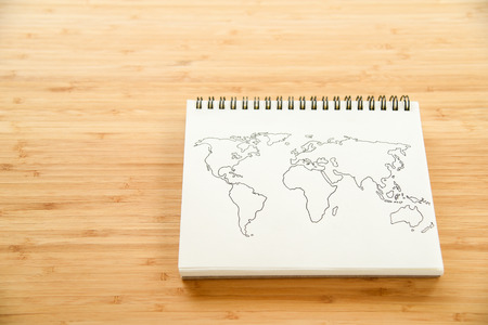 world map outline: World map outline sketch on paper of binder notebook that placed on wooden floor background - can use for travel business or save the earth concepts Stock Photo