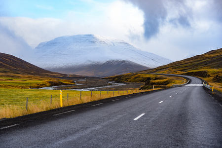 snow covered mountains: Empty road leading to snow covered mountains, Beautiful landscape in early winter of Iceland