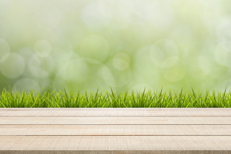 enviro: Beige wood table top panel and grass on green nature blurred background, use for display or montage products for advertisement in spring environmental concept