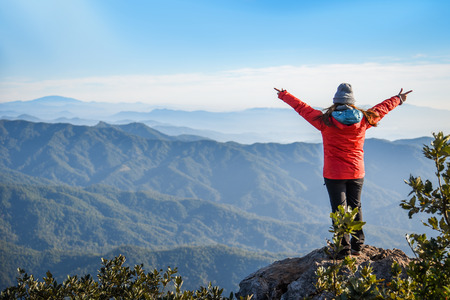 upraised: Woman traveler in red coat climb on the rock and upraised arms on top of mountain among beautiful spring landscape - can use for joy or travel concept