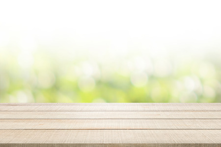 enviro: Beige wood table top panel on green nature blurred background, use for display or montage products for advertisement in spring environmental concept Stock Photo