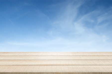 enviro: Beige wood table top panel texture on blue sky and clouds blurred background, use for display or montage products for advertisement in summer environmental concept
