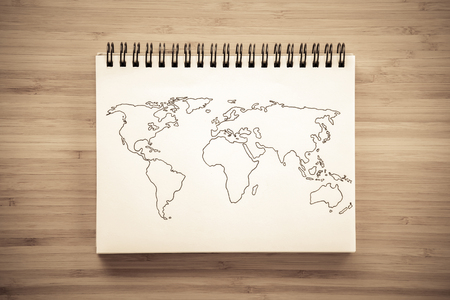 world map outline: World map outline sketch on paper of binder notebook that placed on vintage wooden floor background - can use for travel business or save the earth concepts Stock Photo