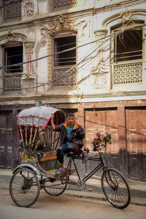 nepali: KATMANDU, NEPAL - APRIL 7, 2016 : Traditional nepalese rickshaw parked on the Thamel street with nepali driver. Editorial
