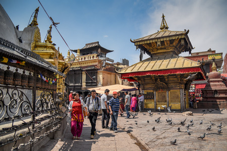 stupa one: KATHMANDU, NEPAL - APRIL 7, 2016 : People walk around Stupa in Swayambhunath (monkey temple), one of famous landmarks in Kathmandu valley, Nepal Editorial
