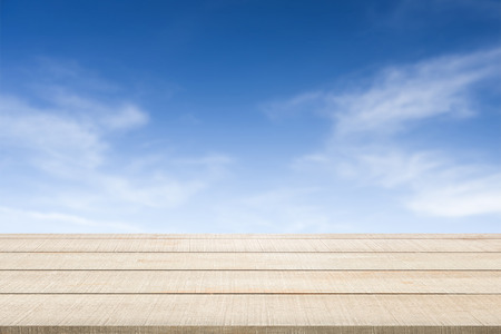 enviro: Beige wood table top panel texture on blue sky and clouds blurred background, use for display products advertisement in natural summer concept