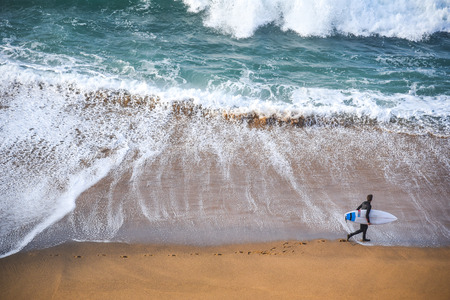 surfer man on the beach with turquoise-white water wave in the sea from top view at Bells beach, Torquay, Australia.