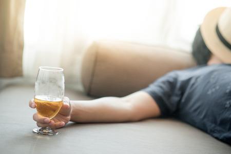 Betrunkener Mann schläft, während er ein Glas Bier im Schlafzimmer hält, Kater nach der Weihnachtsfeier, Alkoholismus oder Alkoholabhängigkeitskonzepte Standard-Bild - 78195194