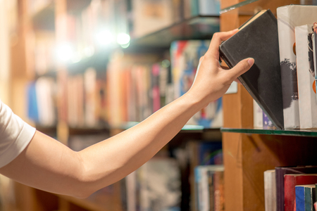 Right hand of young man picking a book from bookshelf in library, reading and learning concepts