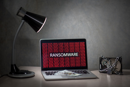 laptop computer screen with ransomware attack alert in red digital binary background with hard disk drive lock, Cyber attack concept