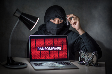 Hacker holding the key with laptop computer screen showing ransomware attacking, alert in red digital binary background with hard disk drive lock. Cyber attack concept Archivio Fotografico