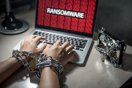 モニターとハード ディスク ファイルがロックされているコンピューターのラップトップ、ユーザー手チェーンとロック コンセプトによって縛りつ 写真素材