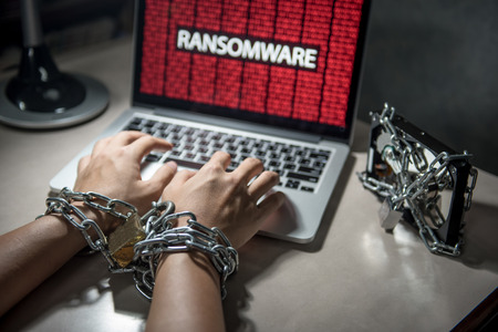 Hard disk file locked with monitor show ransomware cyber attack internet security breaches on computer laptop, user hand tied up by chains and lock concept Archivio Fotografico