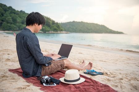 Młody człowiek azjatyckich pracujący z laptopem na tropikalnej plaży, cyfrowy styl życia nomadów lub koncepcje pracy niezależnych