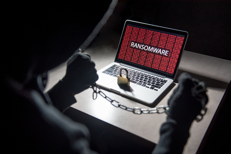 Male hacker locking computer by using chain and padlock, malware ransomware Trojan concept. Internet security concept