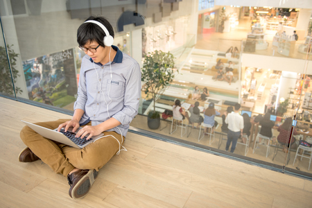 Young Asian man dressed in casual style working with his laptop while listening to music. Digital nomad working in co working space, modern IT lifestyle with work life balance concept. Stock Photo