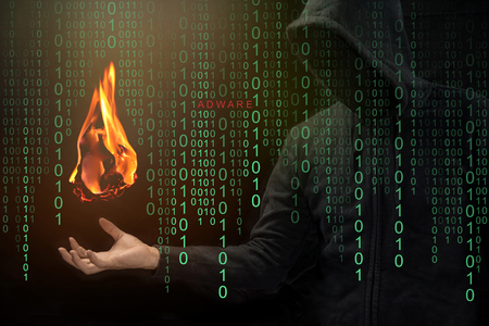 Hacker show a fireball on his hand with green digital binary in foreground. Stock Photo