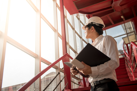 Young Asian Engineer or Architect holding files while wearing personal protective equipment safety helmet at construction site. Engineering, Architecture and building construction concepts Stockfoto
